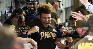 Josh Naylor #22 of the San Diego Padres is congratulated in the dugout after hitting a three-run home run during the eighth inning of a baseball game against the Colorado Rockies at Petco Park August 9, 2019 in San Diego, California. (Photo by Denis Poroy