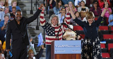 Democratic candidate for Nevada's 4th House District Steven Horsford, U.S. Rep. Dina Titus (D-NV) and Democratic candidate for Nevada's 3rd House District Susie Lee hold hands and raise their arms after speaking during a get-out-the-vote rally