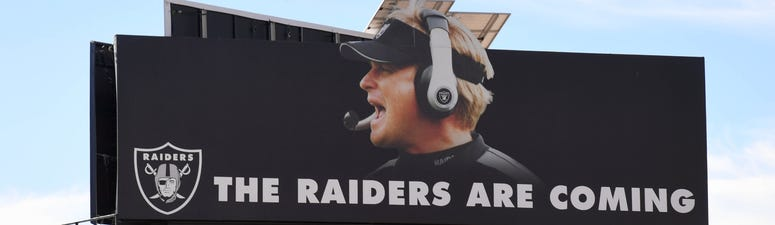 "A billboard featuring the words ""THE RAIDERS ARE COMING"" and an image of Oakland Raiders head coach Jon Gruden is seen on the construction site of the Raiders USD 1.8 billion, glass-domed stadium on December 20, 2018"