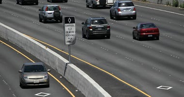"""A Toyota Prius with a California """"clean air vehicle"""" sticker drives in the carpool lane on highway 101 on May 6, 2011 in San Rafael, California."""