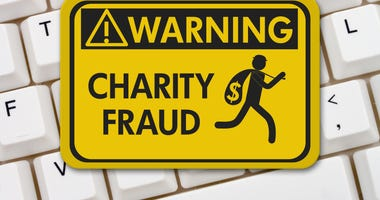 Charity Scam warning sign, A yellow warning sign with text Charity Fraud and theft icon on a keyboard