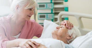 Daughter visiting her senior mother in hospital