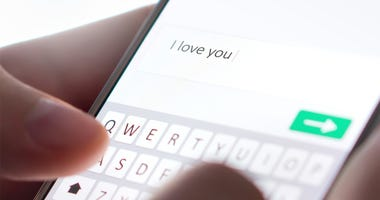 Sending I love you text message with mobile phone. Online dating, texting or catfishing concept. Romance fraud, scam or deceit with smartphone. Man writing comment. Fake profile. Internet safety