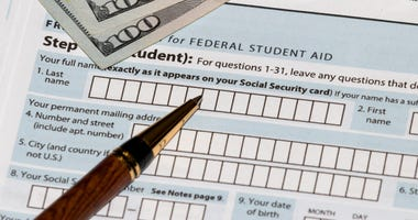 Student financial aid application forms for college tuition loans and grants with one-hundred dollar bills and ballpoint pen