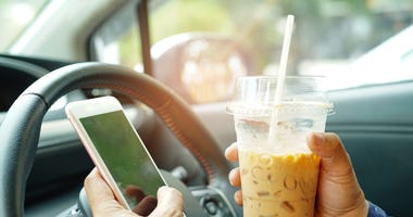 Woman trying to drive while texting and holding coffee