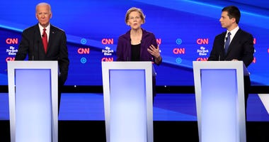 Sen. Elizabeth Warren (D-MA) (C) speaks as former Vice President Joe Biden and South Bend, Indiana Mayor Pete Buttigieg look on during the Democratic Presidential Debate at Otterbein University on October 15, 2019 in Westerville, Ohio.