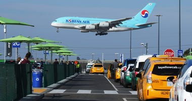 A Korean Air plane lands as taxis are lined up at the new 'LAX-it' ride-hail passenger pickup lot at Los Angeles International Airport (LAX) on November 6, 2019 in Los Angeles, California.
