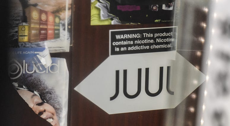 A sign advertising JUUL products is displayed in a store on December 19, 2019 in New York City. Congress raised the legal age to smoke or vape to 21.