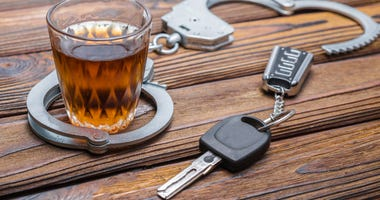 Drunk driving concept, with handcuffs, a glass of alcohol, car keys