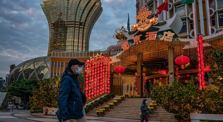 People wearing face masks walk in front of the Grand Lisboa Hotel on January 28, 2020 in Macau, China.