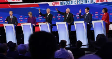 Tom Steyer (L) speaks as (L-R) Sen. Elizabeth Warren (D-MA), former Vice President Joe Biden, Sen. Bernie Sanders (I-VT) and former South Bend, Indiana Mayor Pete Buttigieg (R) react during the Democratic presidential primary debate at Drake University