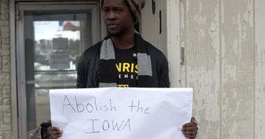 Local resident Wallace Mazon holds a sign outside the Iowa Democratic Party headquarters February 4, 2020 in Des Moines, Iowa.