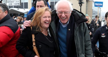 Democratic presidential candidate Sen. Bernie Sanders (I-VT) and his wife, Jane Sanders, walk together after greeting people campaigning for him outside of a polling station on February 11, 2020