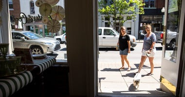 People walk between shops and restaurants that have reopened this week following loosening of non essential business restrictions on May 2, 2020 in Franklin, Tennessee
