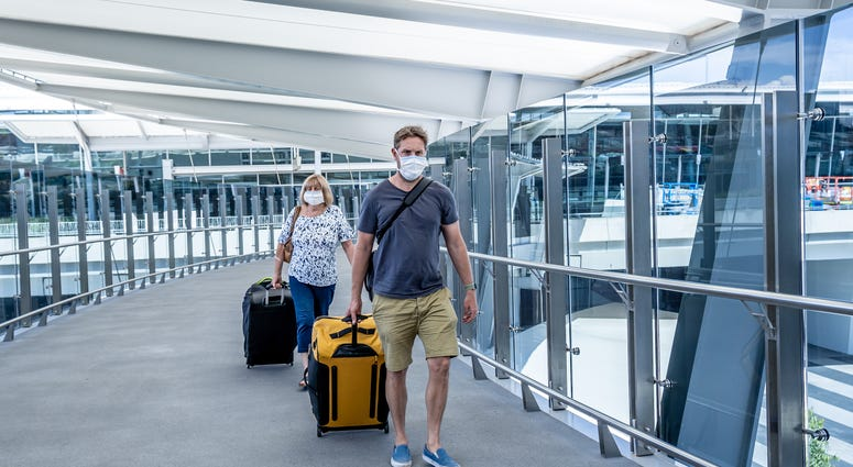 enior woman and adult son wearing face mask at airport in fear of coronavirus and travel ban and international trips cancellations for disease control and prevention of COVID-19 outbreak pandemic.