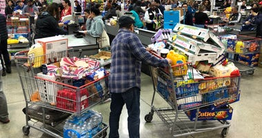 A Costco customer stands by his two shopping carts at a Costco store on March 13, 2020 in Richmond, California