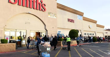 Shoppers leave with groceries as others wait for their turn to enter a Smith's Food & Drug store on March 20, 2020 in Las Vegas, Nevada.