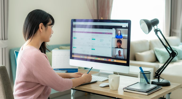 Back view of Asian business woman talking to her colleagues about plan in video conference.