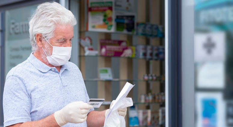 Elderly man with mask and protective gloves leaves the chemist's shop with medicines and instructions.