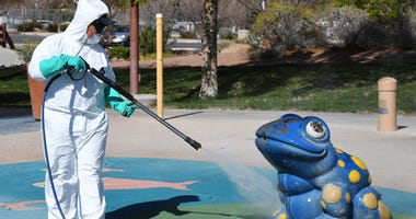 City of Las Vegas operations and maintenance staff worker Denis Connelly pressure washes playground equipment at Centennial Hills Park as part of an effort to keep the city's 70 parks open for the public during the coronavirus pandemic on March 25, 2020 i