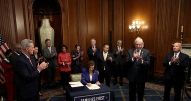 Speaker of the House Nancy Pelosi (D-CA), surrounded by a bipartisan group of members of the House, signs the stimulus bill known as the CARES Act after the bill was passed at the U.S. Capitol on March 27, 2020 in Washington, DC.