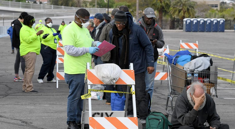 'Help of Southern Nevada' workers check in homeless people as they line up at a temporary homeless shelter set up in a parking lot at Cashman Center on March 28, 2020 in Las Vegas