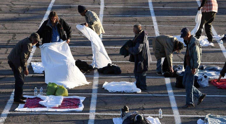 People arrive at a temporary homeless shelter with painted social-distancing boxes in a parking lot at Cashman Center on March 30, 2020 in Las Vegas, Nevada