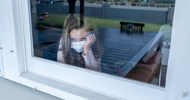 Depressed lonely little girl with face mask looking through the window during quarantine.
