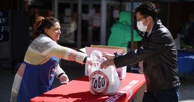 Silver Diner senior marketing manager Cindy Sabana (L) helps hand out 400 free meals outside the restaurant during the coronavirus pandemic April 02, 2020 in Gaithersburg, Maryland