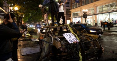 Protesters riot in the streets following a peaceful rally expressing outrage over the death of George Floyd on May 30, 2020 in Seattle