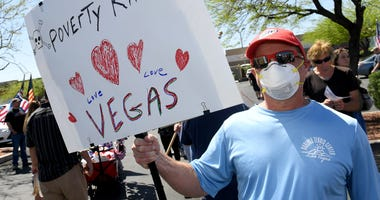 Mike Giletto of Nevada holds a sign as people gather for a protest caravan along the Las Vegas Strip