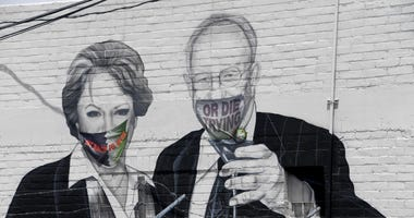 A mural on the side of the Majestic Repertory Theater depicts Las Vegas Mayor Carolyn Goodman (L) and her husband, former Las Vegas Mayor Oscar Goodman, with masks added over their faces in the downtown Arts District amid the spread of the coronavirus on
