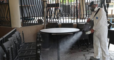 Edwin Britto, from Copax llc.) sprays a decontamination fog as he sanitizes a restaurant before it opens on May 18, 2020 in Fort Lauderdale, Florida.