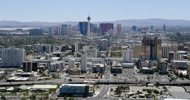 An aerial view shows hotel-casinos and other venues downtown (foreground) and on the Las Vegas Strip