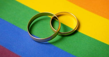 same-sex marriage- two wedding rings on lgbt rainbow flag