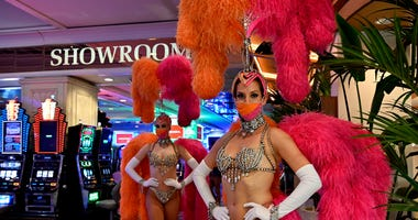 Showgirl Brittany Guinane (R) and Katie Wolfe, wearing face masks, pose at Flamingo Las Vegas on the Las Vegas Strip after the property opened for the first time since being closed on March 17 because of the coronavirus (COVID-19) pandemic