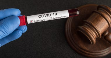 Blood samples in sample tube with label COVID 19 and judges gavel. Quarantine and law against covid-19.