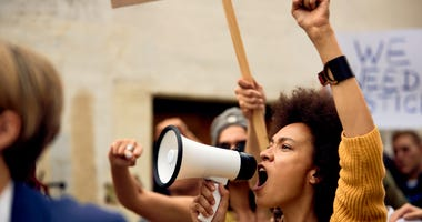 Young African American woman with raised fist shouting through megaphone while being on anti-racism protest