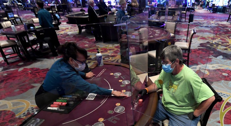 Nila Davis (L) deals cards to Becky Lewis of Texas at a blackjack table with plexiglass safety shield dividers at Excalibur Hotel & Casino after the Las Vegas Strip