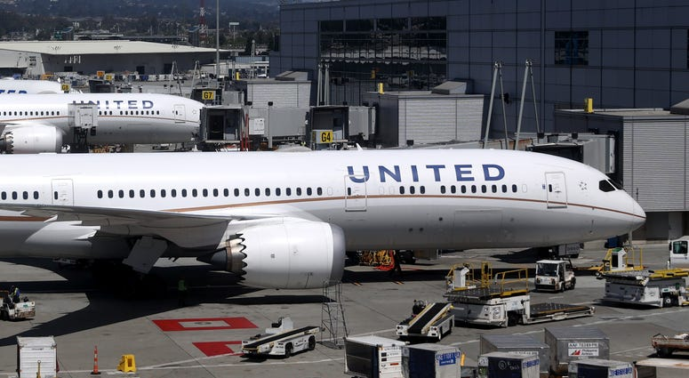 United Airlines workers load cargo onto a plane at San Francisco International Airport on July 08, 2020 in San Francisco, California.