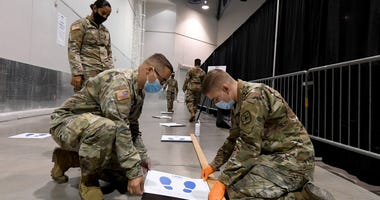 Members of the Nevada National Guard Pfc. Erika Garcia, Spc. Austin Stolpe and Pfc. Josh Wood put down social distancing decals at a new coronavirus (COVID-19) testing site inside Cashman Center on August 3, 2020