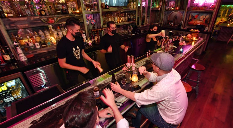 Barback Jaime Torres, bar manager Chance Bennett and bartender Brandi Sterner work behind the bar as Pete Cangelosi (L) and his friend Mike Silva, both of Louisiana, become the first patrons to sit at the bartop after it opened