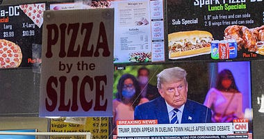 President Donald Trump is seen through a television at a takeout pizza shop in the U street corridor as he speaks during a town hall on October 15, 2020