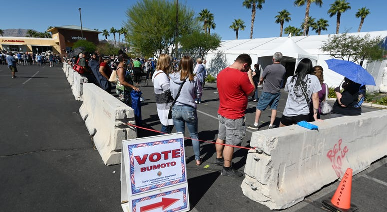 People line up to vote at a shopping center on the first day of in-person early voting on October 17, 2020 in Las Vegas, Nevada. Early voting for the general election in the battleground state continues through October 30.