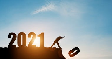 Man push number zero down the cliff where has the number 2021 with blue sky and sunrise. It is symbol of starting and welcome happy new year 2021