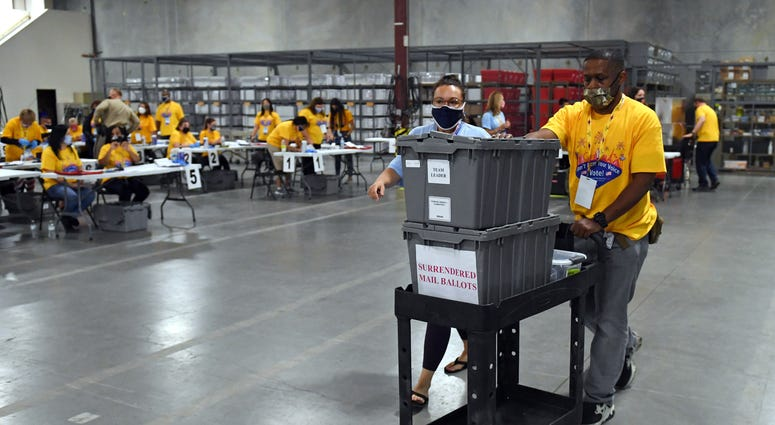 Workers process polling place equipment and materials at the Clark County Election Department after polls closed on November 3, 2020 in North Las Vegas,