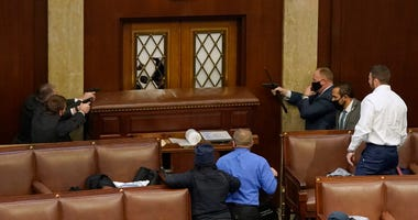 U.S. Capitol police officers point their guns at a door that was vandalized in the House Chamber during a joint session of Congress on January 06, 2021 in Washington, DC