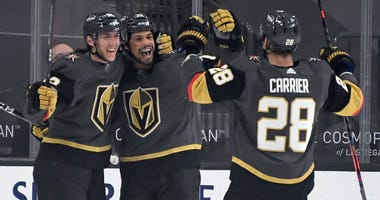 Tomas Nosek #92, Ryan Reaves #75 and William Carrier #28 of the Vegas Golden Knights celebrate after Reaves assisted Nosek on a first-period goal against the Anaheim Ducks at T-Mobile Arena on January 14, 2021 in Las Vegas, Nevada.