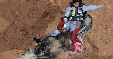 "Scott Schiffner of Canada rides ""Pudd"" during the Professional Bull Riders World Finals"