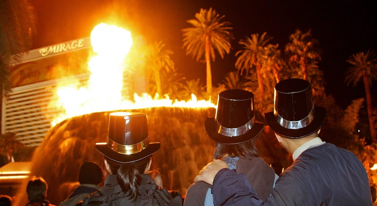 Revelers watch the volcano attraction at The Mirage Hotel & Casino during New Year's Eve festivities on the Las Vegas Strip